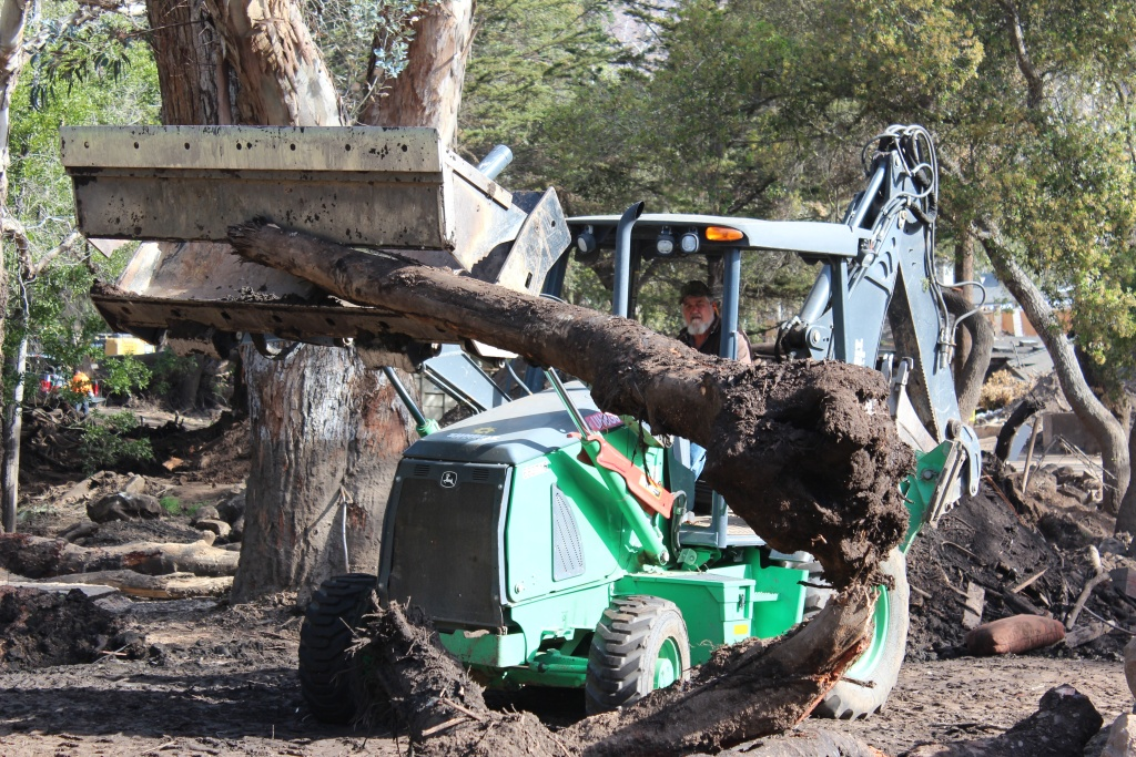On Thurs., March 8, 2018, cleanup crews worked to clear tree trunks swept downhill from a debris flow in Montecito two months earlier.