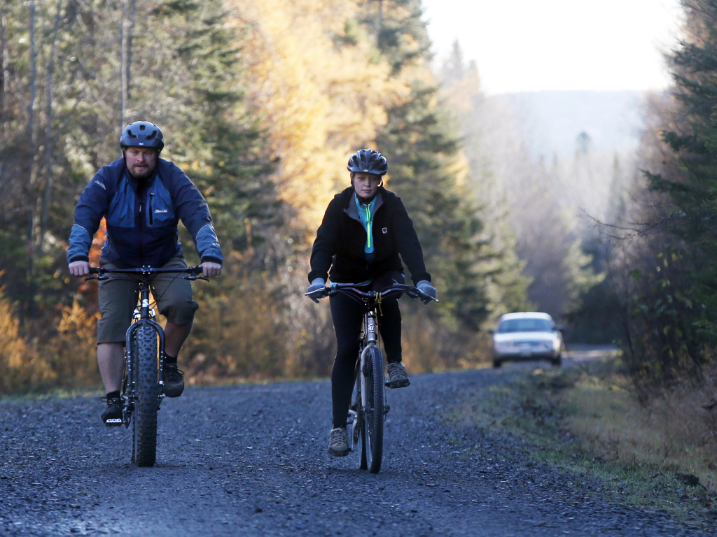 Nurse Kaci Hickox, right, and her boyfriend, Ted Wilbur are followed by a Maine State Trooper as they ride bikes on a trail near her home in Fort Kent, Maine, on Thursday.