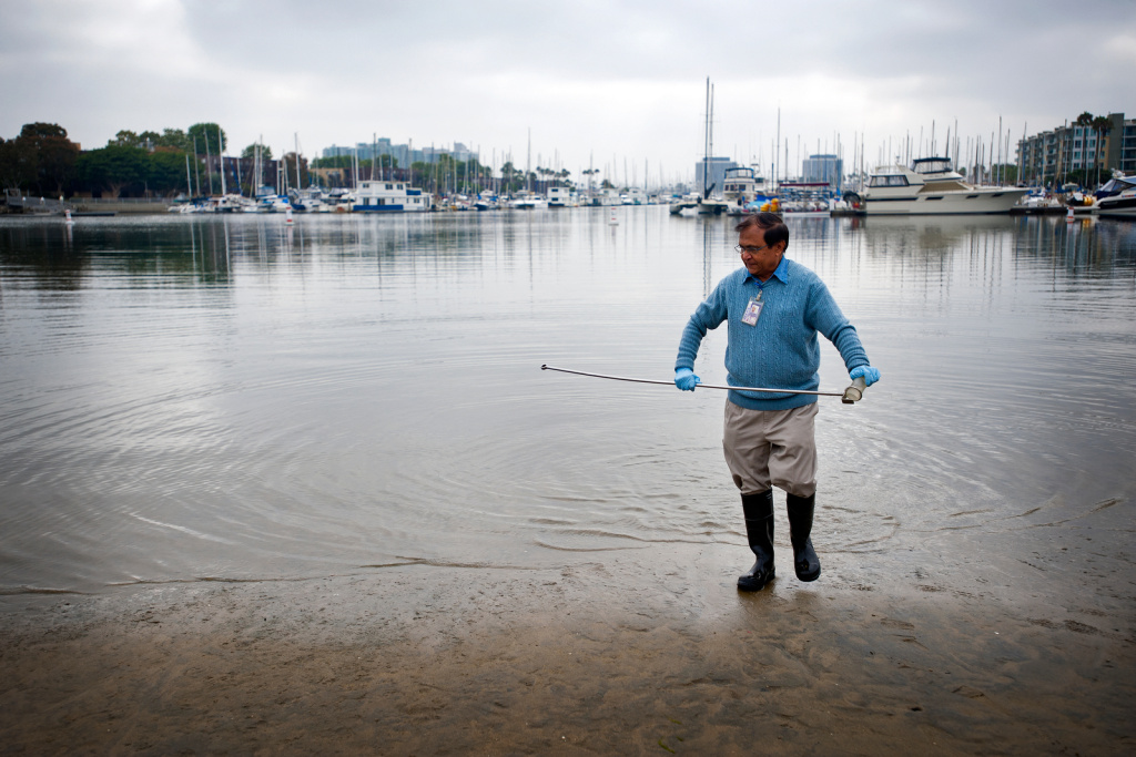 Pravin Patel, a lab technician in the Environmental Monitoring Division for Los Angeles County, takes samples of the beach water in Marina del Rey.