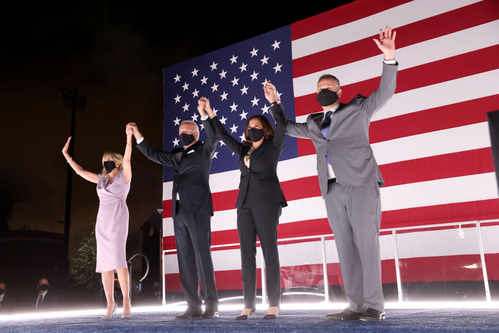Democratic presidential nominee Joe Biden, his wife Dr. Jill Biden, Democratic Vice Presidential nominee Kamala Harris and her husband Douglas Emhoff raise their arms on stage outside the Chase Center after Biden delivered his acceptance speech on the fourth night of the Democratic National Convention from the Chase Center on August 20, 2020 in Wilmington, Delaware.