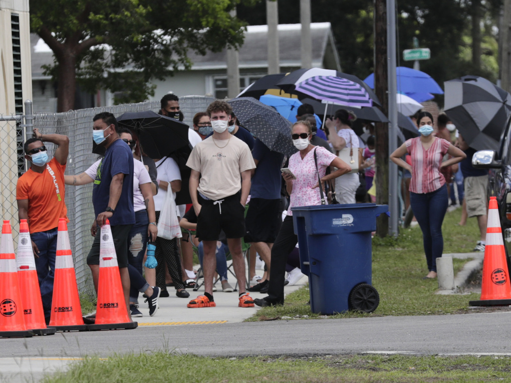 People wait in line outside of a COVID-19 testing site in Florida. The state has seen unprecedented surges in coronavirus cases in recent weeks.