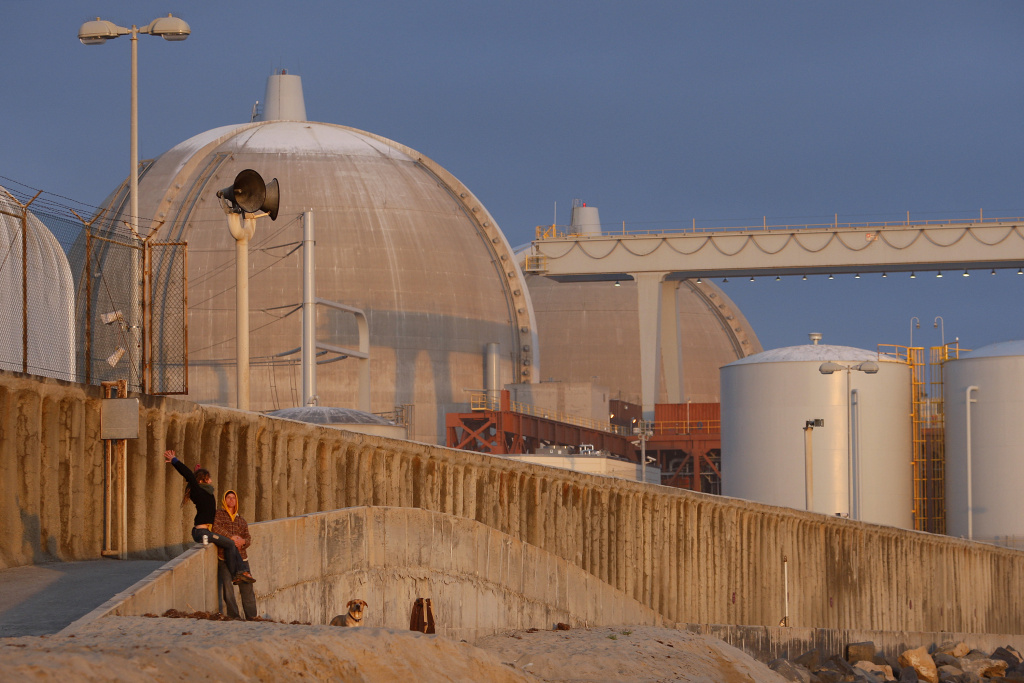 A couple stands near the San Onofre Nuclear Generating Station at San Onofre State Beach on March 15, 2012 south of San Clemente.
