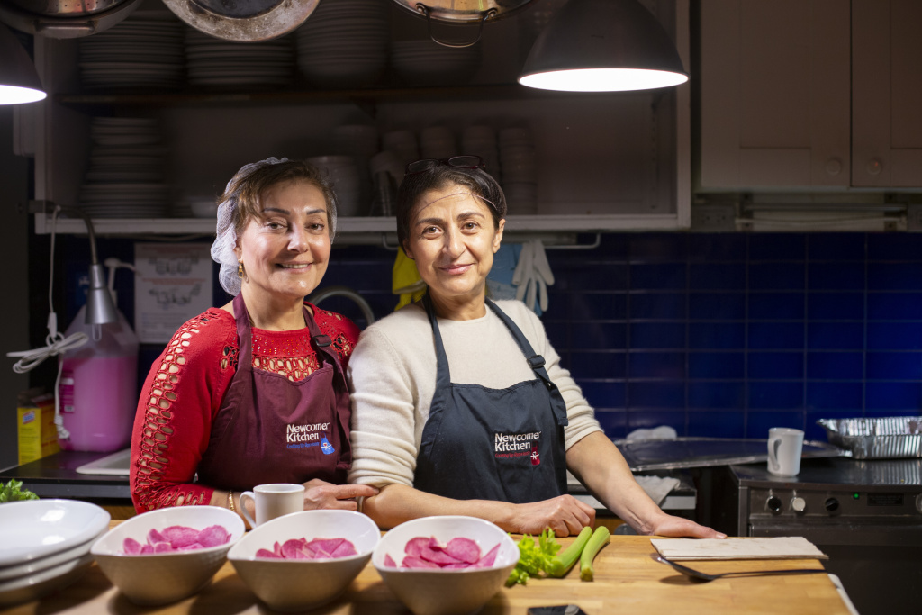 Two Syrian refugees, Narwal Alakayleh (left) and Lina AlAlssantin (right), prepare for a pop-up dinner of Levantine food at Newcomer Kitchen.