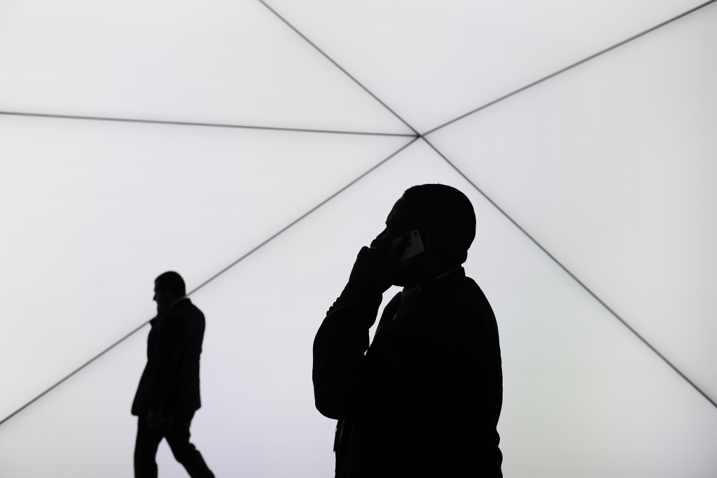Caption:A visitor speaks on his phone in Barcelona on February 25, 2014, on the second day of the 2013 Mobile World Congress.