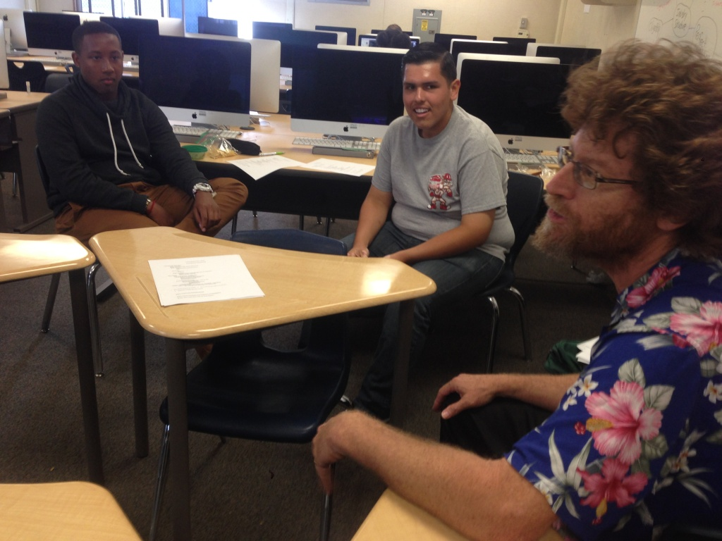 Long Beach Poly High School economics teacher Dan Adler, right, leads a meeting of students who've helped low income residents fill out their tax returns.