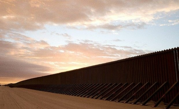 A stretch of border fence through the desert, Imperial Sand Dunes, California.