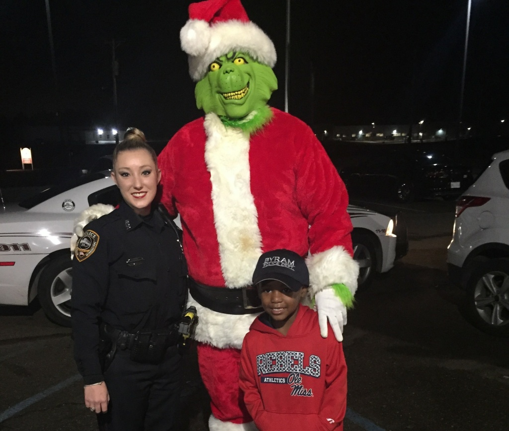 Officer Lauren Develle with TyLon Pittman and the Grinch, who did not steak Christmas.
