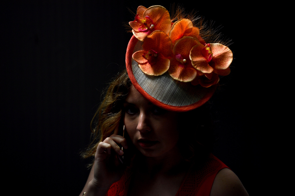A woman in a festive hat talks on the phone before the 143rd Kentucky Derby on May 6, 2017 at Churchill Downs in Louisville, Kentucky.