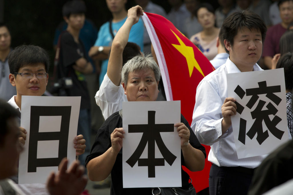Anti-Japan protesters hold printed Chinese characters, that reads