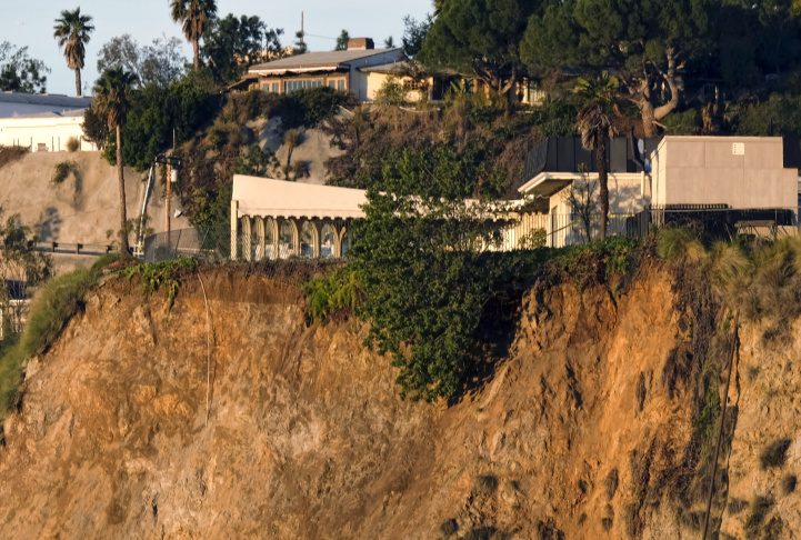A broken utility poll remains standing, left, as a deck of a home, right, juts out precariously over an area where a landslide occurred in the Hollywood Hills area of Los Angeles on Tuesday, Jan. 31, 2017. City inspectors are at a Hollywood Hills home where the backyard crumbled, sending mud and debris down a slope, across a street and into the front yards of two other houses.