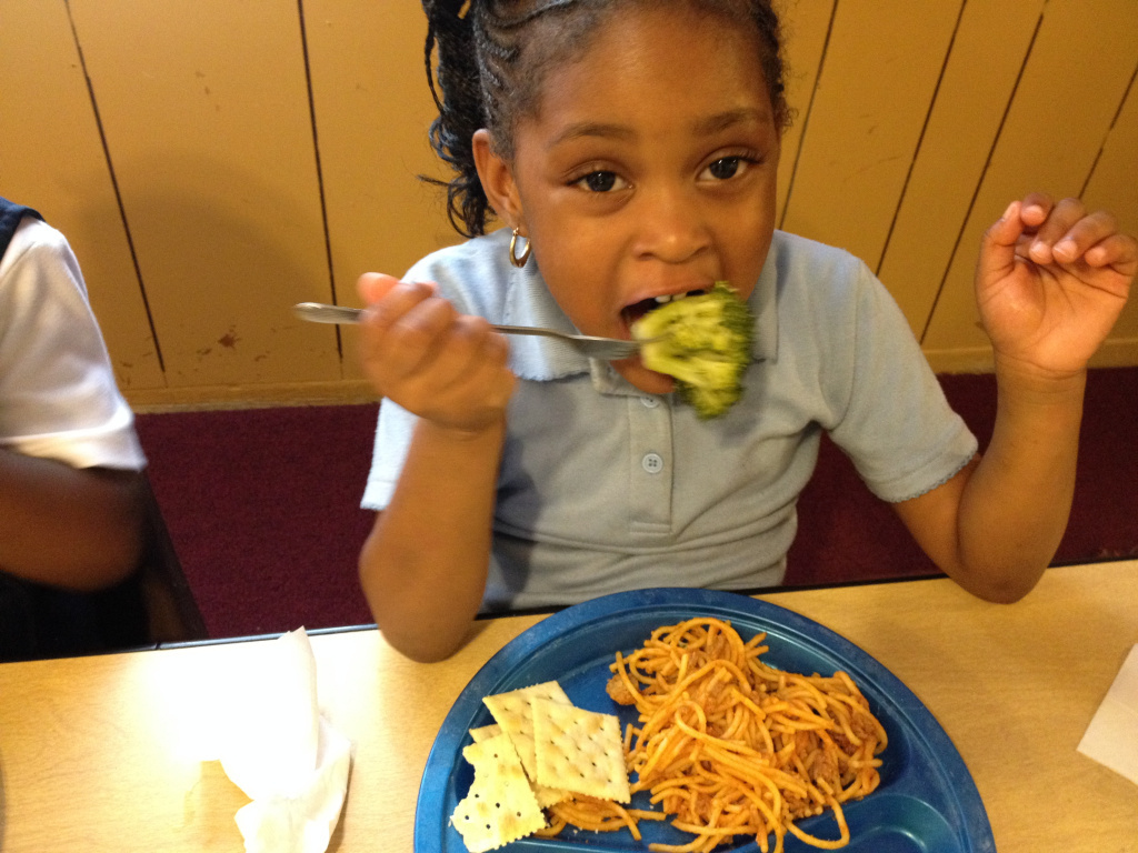 Preschooler eats her broccoli at lunch at Little Lambs Child Care center.