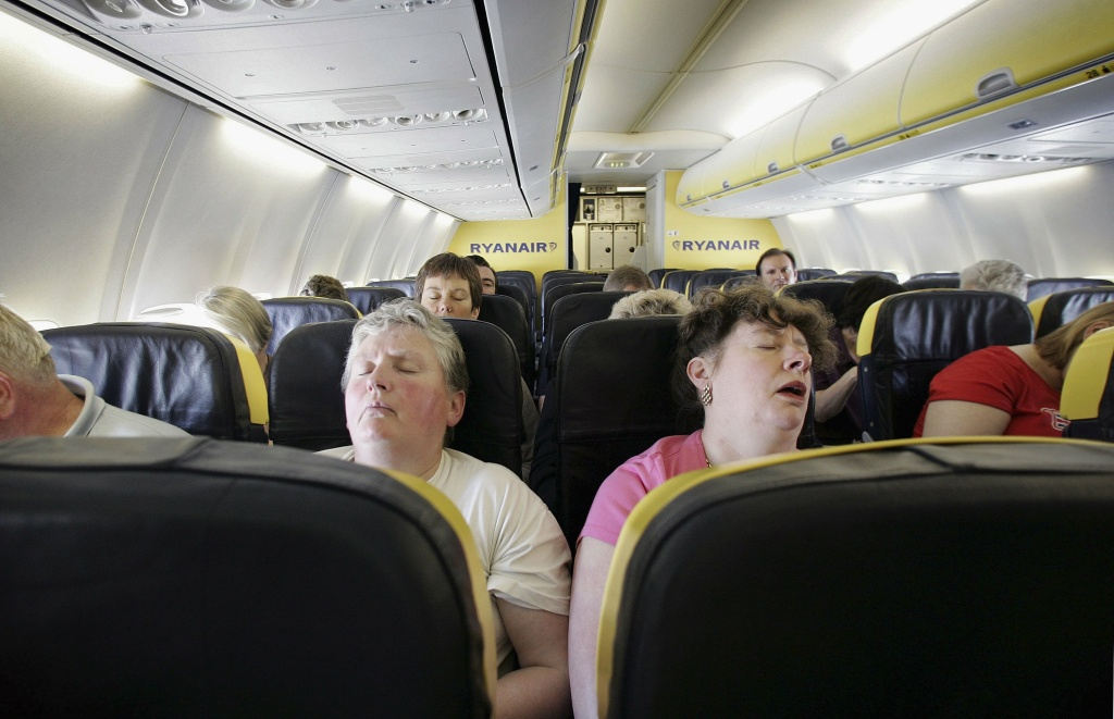 Passengers sleep on a low cost flight to Dinard in France on May 15, 2006 from London.