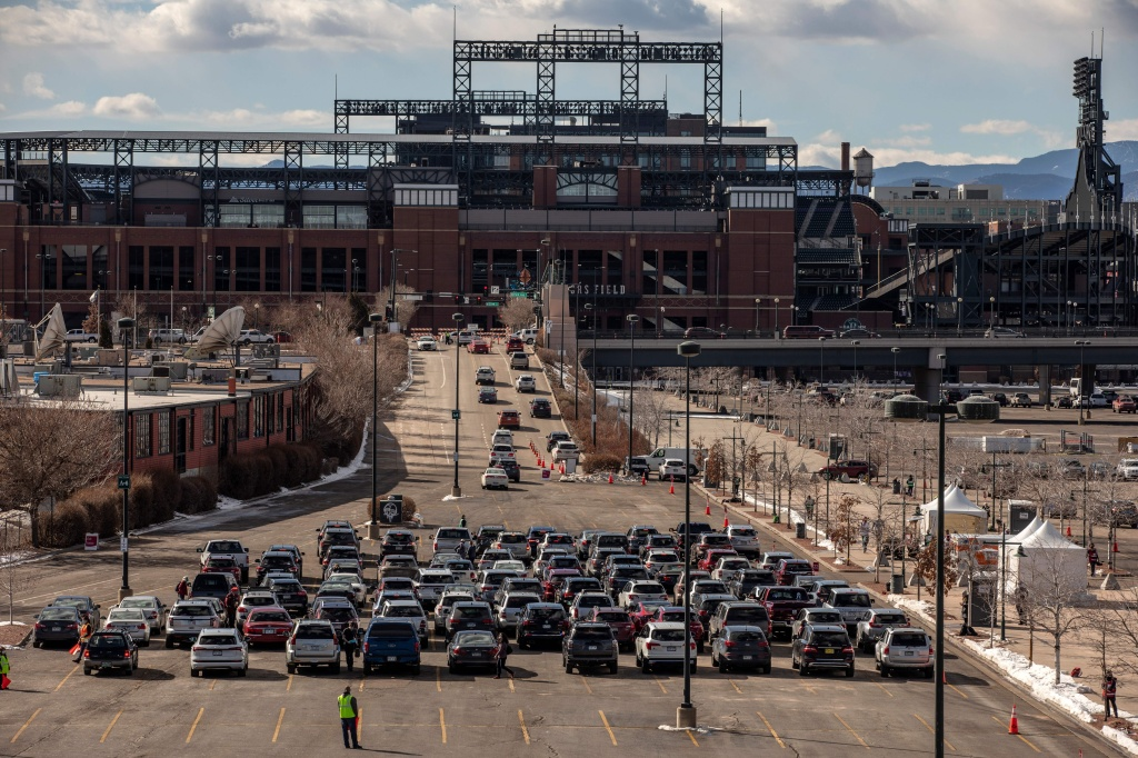 People line up for drive-through COVID-19 vaccination at Coors Field baseball stadium in Denver on Saturday.