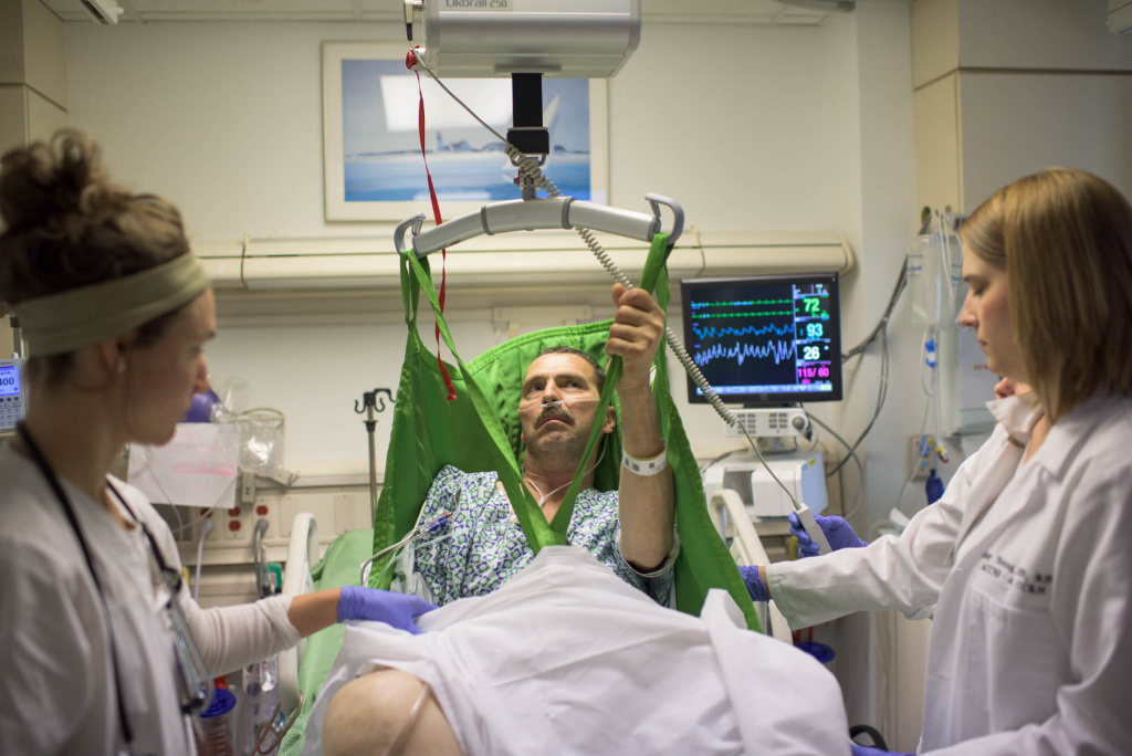 Nurses Katherine Malinak and Amy Young lift Louis DeMattio, a stroke patient, out of his hospital bed using a ceiling-mounted lift at the Cleveland Clinic.