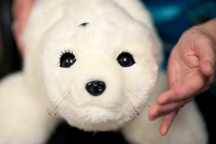 """Robotic baby harp seal """"Paro"""" has numerous sensors and responds to voices, petting and light by squealing, blinking and moving its head, tail and flippers."""