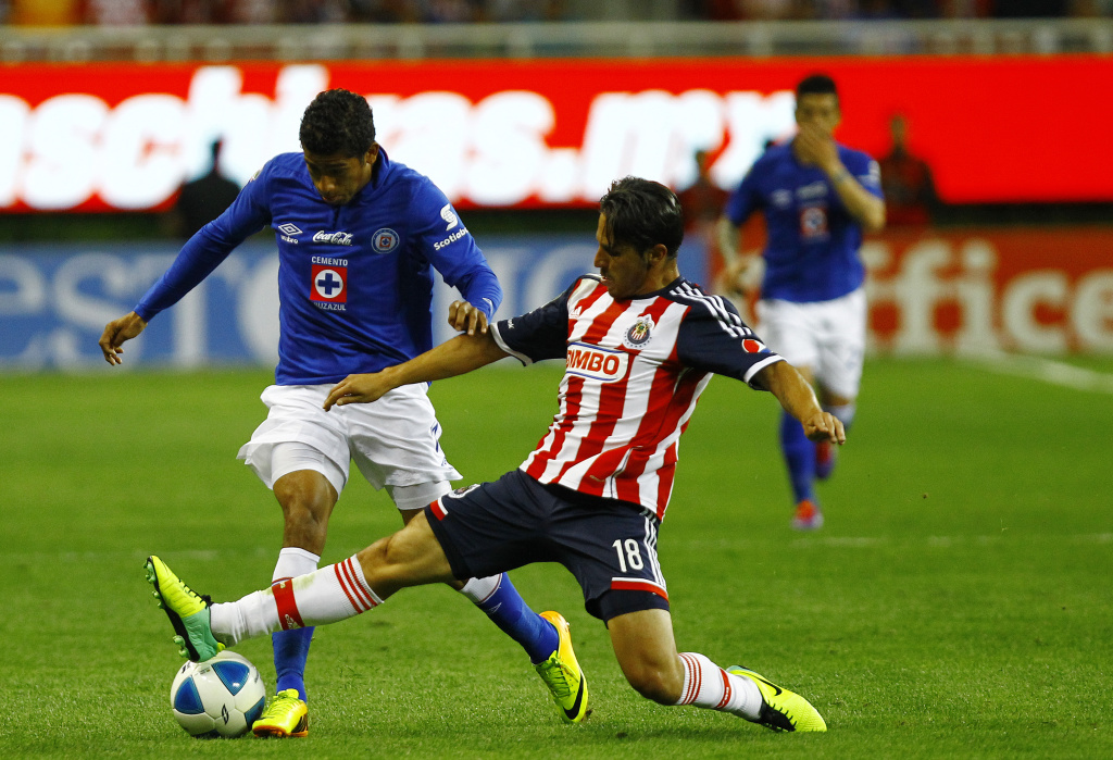Edgar Solis(R) of Chivas vies for the ball with Joao Rojas(L) of Cruz Azul during their Clausura 2014 Mexican tournament football match at the Omnilife stadium on February 01, 2014 in Guadalajara city, Mexico.