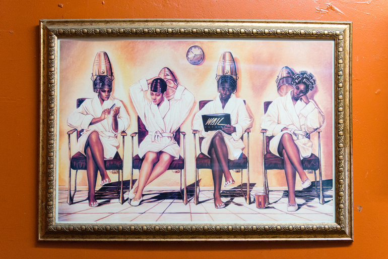 Art hangs in the barbershop.