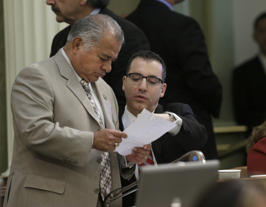 In this file photo, Assemblyman Rocky Chavez, R-Oceanside, left, talks with Assemblyman Bob Blumenfield, R-Woodland Hills, chairman of the Assembly budget committee, as the Assembly worked on the state budget at the Capitol, Friday, June 14, 2013 in Sacramento, Calif. Chavez had been running to replace outgoing U.S. Senator Barbara Boxer, but on Monday he abruptly announced he was dropping out.