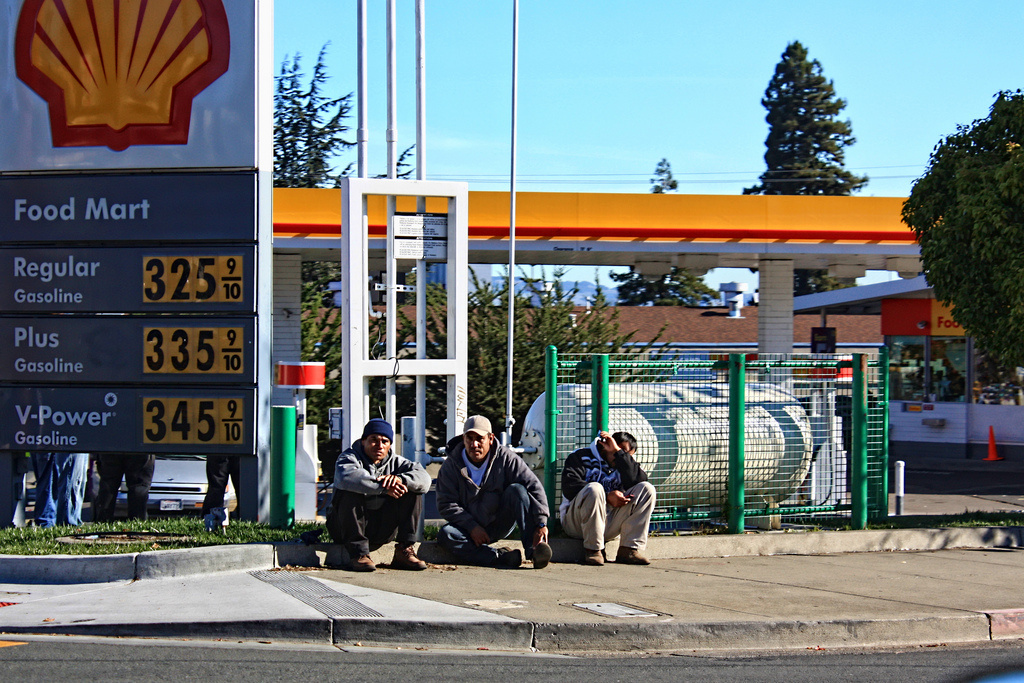 Day laborers sit in front of a Shell gas station in California.