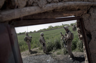 A US Marine (2nd R) of 3rd Battalion, 6th Marines checks their position on a GPS device as they move forward at a farm during a foot patrol in Marjah, Helmand province, on April 3, 2010.