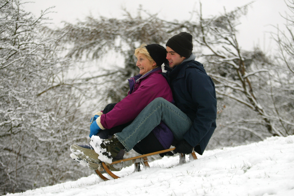 A woman and her son go tobogganing in a park in England.