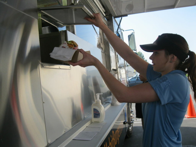 An employee from The Habit grabs a cheeseburger order from the burger chain's food truck.