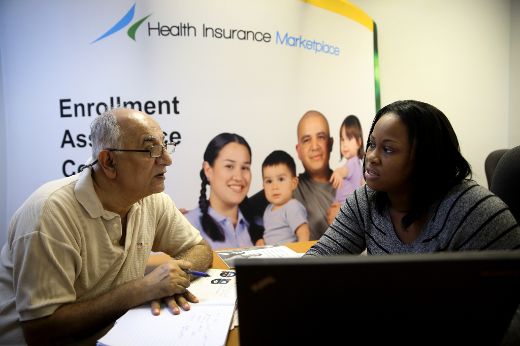 Narendra Parmar sits with Certified Enrollment Specialist, Laquanda Jordan, as he finishes the process of picking and signing up for health insurance through the Affordable Care Act at a Miami Enrollment Assistance Center on December 23, 2013 in Miami, Florida.
