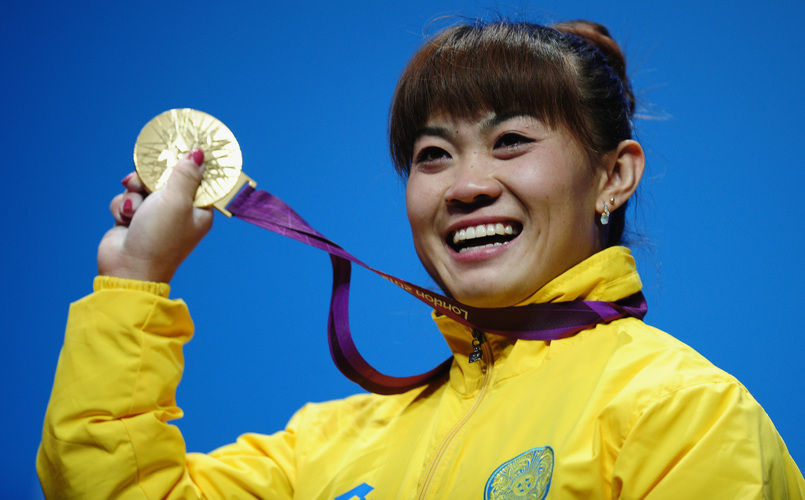 Weightlifter Maiya Maneza of Kazakhstan celebrates on the podium with her new 400-gram gold medal, matching the feat of her compatriot Zulfiya Chinshanlo. The Kazakh Olympians will each receive a $250,000 bonus.
