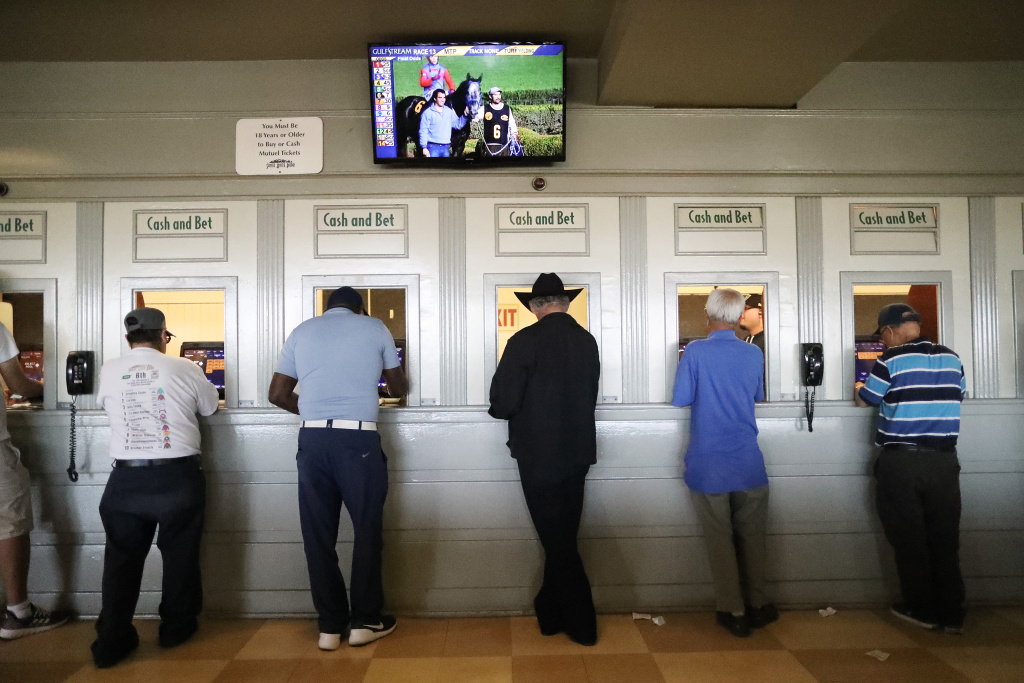 Gamblers stand at betting windows at Santa Anita Park in Arcadia, California.