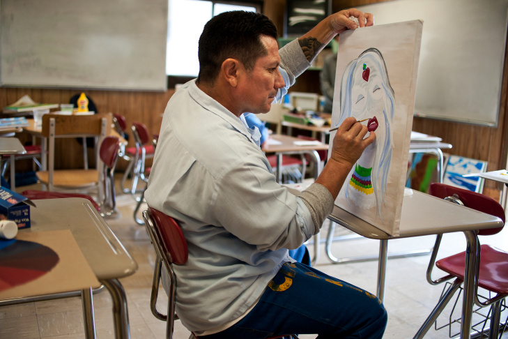 Jesus Ledesma works on a painting inspired by Day of the Dead sugar skulls. The three-hour painting class takes place once a week in a small trailer classroom. Ledesma is serving a six-year sentence for injuring another man in a fight.