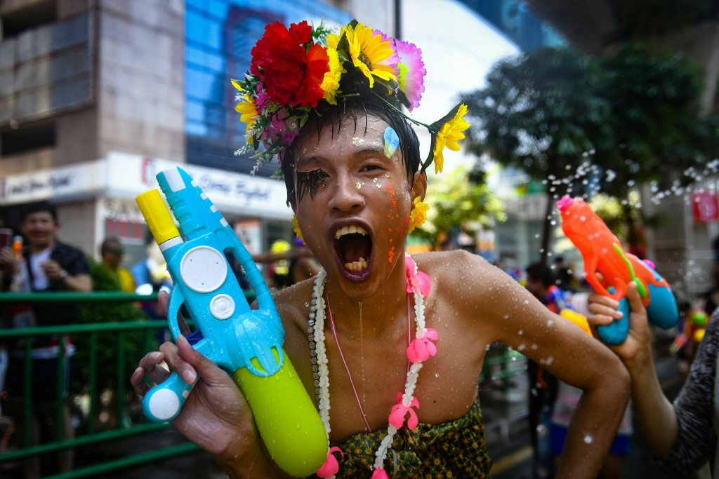 A reveller wearing a colorful costume holds a toy water gun during a mass water fight in celebration of Songkran, or Thai New Year, on Silom Road in Bangkok on April 13, 2018.