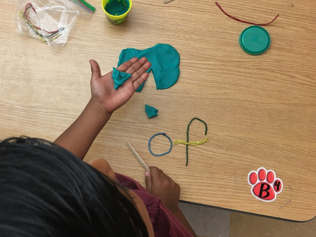 Students in Karen Scannell's kindergarten class at Synergy Charter Academy in South L.A., make a pizza out of playdoh and then cut out a piece