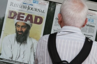A passerby looks at newspaper headlines reporting the death of Osama Bin Laden.