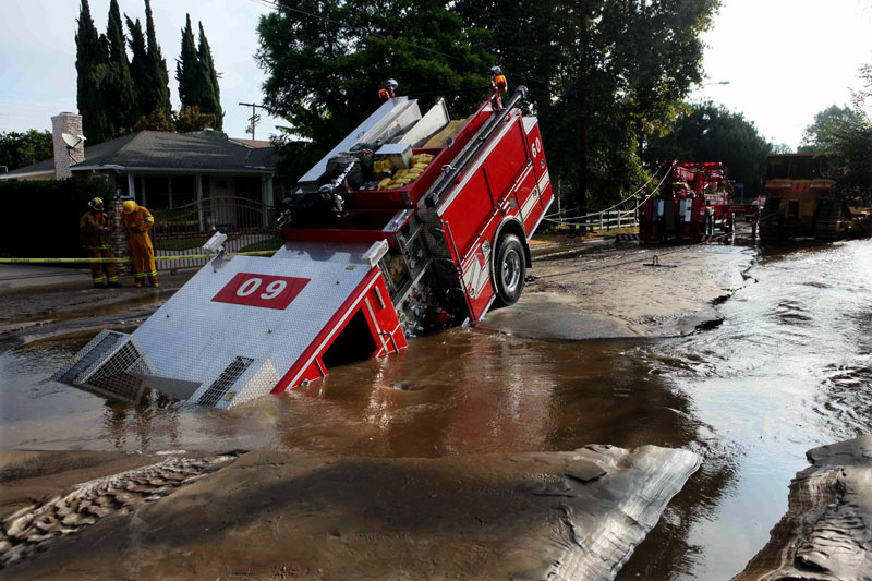A Los Angeles fire truck is pulled from a sinkhole in the Valley Village neighborhood of Los Angeles.