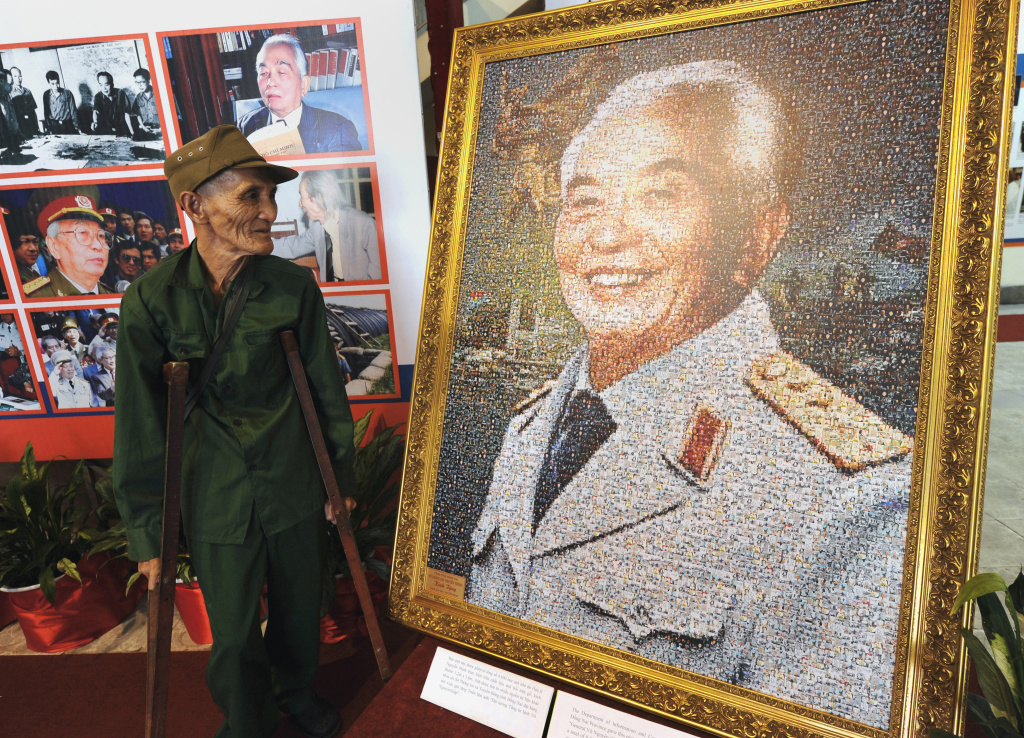 Xuan Hieu (L), 78, a Dien Bien Phu veteran, looks at a portrait of Vietnam's legendary general, Vo Nguyen Giap, displayed at an official photo exhibition on his life in Hanoi on August 25, 2011. General Giap, who drove French and U.S. forces out of Vietnam, died Friday.