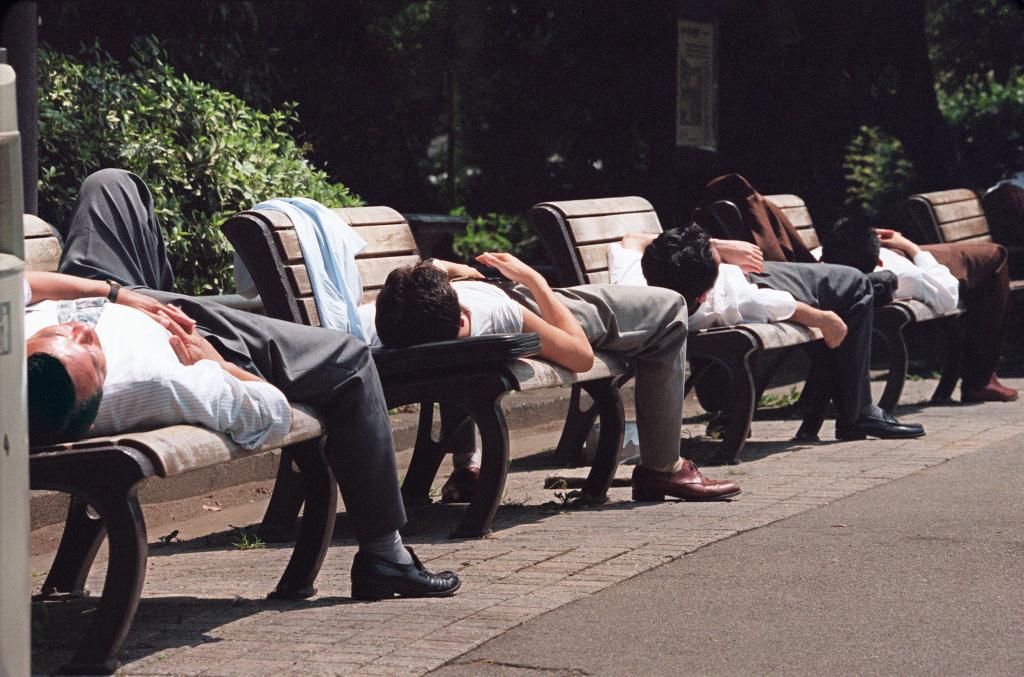 Japanese businessmen take naps on benches in Hibiya park, central Tokyo, 04 August 1994.
