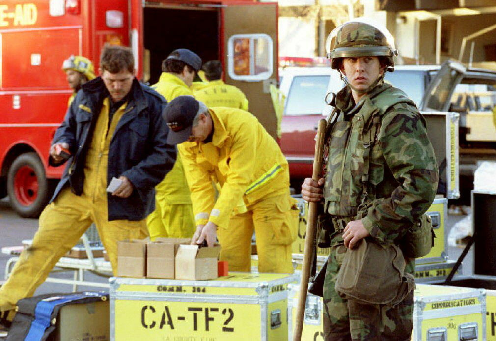 A California National Guard troop stands watch outside the Northridge Meadows Apartments, early Jan. 18, 1994 as rescue workers pack up gear.