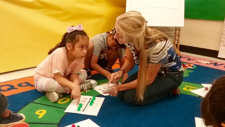 Yurianna Lara, 6, works with deaf and hard-of-hearing teacher Ann Franklin, righty, during a shared reading exercise as part of the innovative