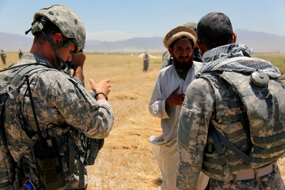 A U.S. Army soldier and interpreter gather information from locals about land owners in Sabikhel, Afghanistan in June 2010.