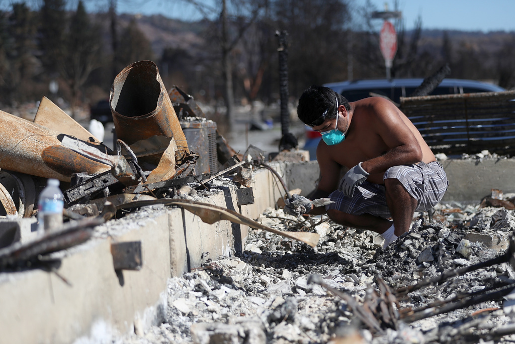SANTA ROSA, CA - OCTOBER 23:  Ben Hernandez sifts through the remains of his Coffey Park home that was destroyed by the Tubbs Fire on October 23, 2017 in Santa Rosa, California. Residents are returning to their homes after a fast moving and deadly widlfire destroyed 8,400 structures and claimed the lives of at least 42 people.  (Photo by Justin Sullivan/Getty Images)