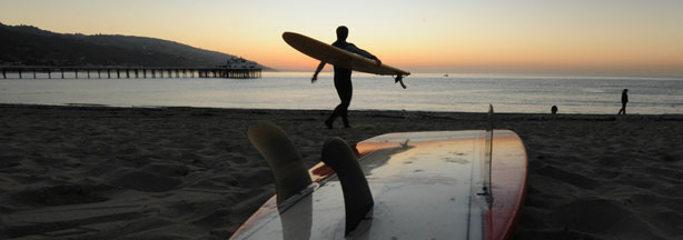 A surfer enters the water at the iconic Malibu Surfrider Beach.