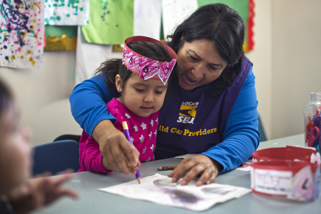 Childcare provider Antonia Rivas works with 2-year-old Selena on a Valentine's Day art project at Rivas Family Child Care in Reseda on Friday morning, Feb. 13.