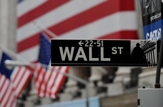 A Wall Street sign is seen against the backdrop of the New York Stock Exchange in New York City
