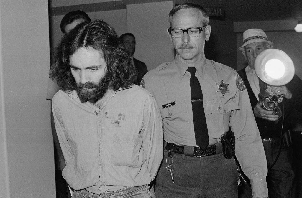 Cult leader Charles Manson stares at the floor, Oct. 6, 1970, as he is led to the Los Angeles court room from which he was ousted the day before after lunging at Judge Charles H. Older with a sharpened pencil clutched in his hand. Manson and three women followers involved in the case will be listening to the proceedings in an adjoining room because of their behavior.