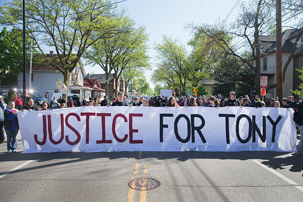 Demonstrators organized by the Young Gifted & Black Coalition pass Tony' Robinson's home May 13, 2015 in Madison, Wisconsin. Tony Robinson, 19, was killed March 6 after officer Matt Kenny responded to several calls claiming Robinson was acting disorderly and violent. Kenny claims he was assaulted by Robinson and shot him in self-defense.