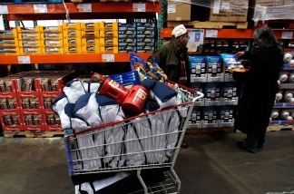 Shoppers stand near a filled cart in a Costco warehouse store.