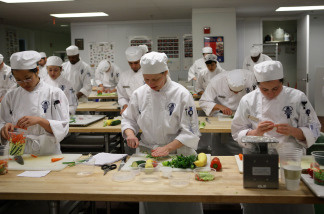 Culinary students do prep work for a meal during a butchery class at the Le Cordon Bleu program at California Culinary Academy in San Francisco, California.
