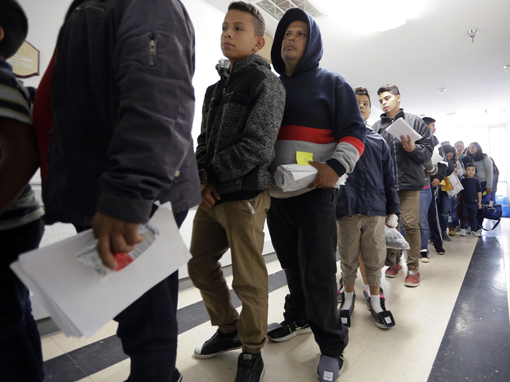 A line of migrants recently released by U.S. immigration authorities waits to check in at the Catholic Charities shelter in McAllen, Texas.