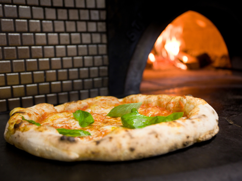 Brick transfers heat to dough more slowly than steel, allowing both pizza crust and toppings to simultaneously reach perfection.