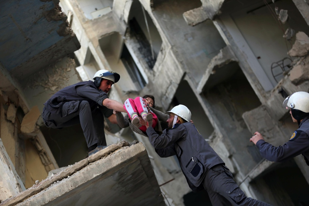 Members of the Syrian Civil Defence, known as the White Helmets, evacuate a child during a training session in the rebel-held eastern Ghouta area, east of the capital Damascus.